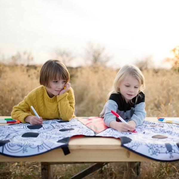 2 enfants sont en train de colorier la cape coccinelle