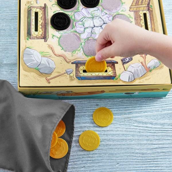 une main d'enfant met une pièce d'or dans la boite du jeu à l'endroit prévu