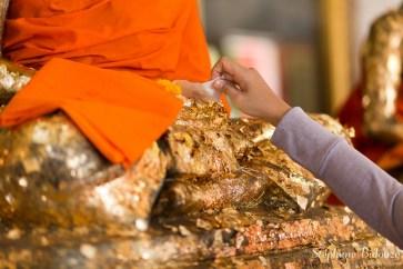 Plaquage d'une feuille d'or sur le Bouddha