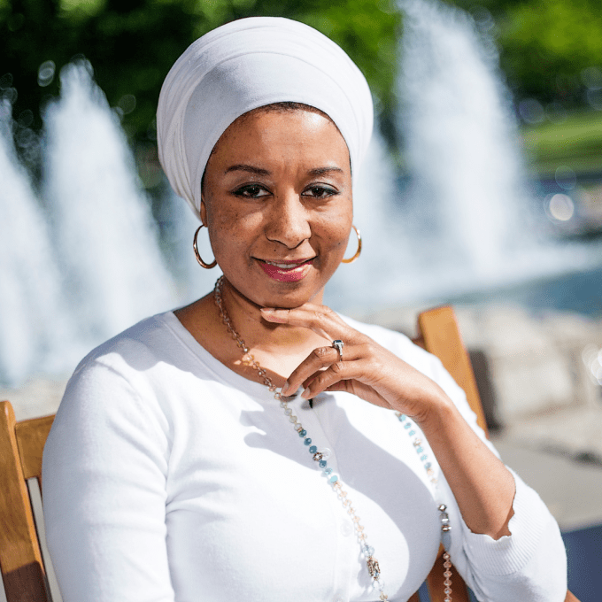 Aisha Sharif sitting in front of a water fountain.