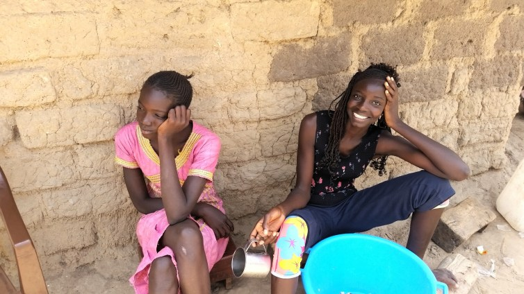 Two of my sisters, Ndaela (right) and Daba (left) taking a break from cooking lunch
