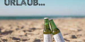 Zwei Bierflaschen stehen auf Sand