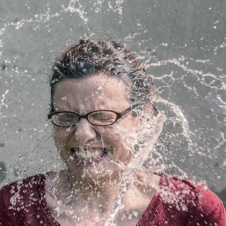 woman wearing glasses with water splashing in her face