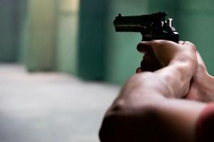 man's hands pointing gun