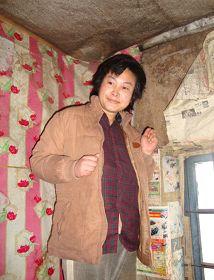 被迫害致瘋的柳志梅,當有人試圖接近,她就攥著雙手躲向自家牆角(攝於二零一零年冬)
