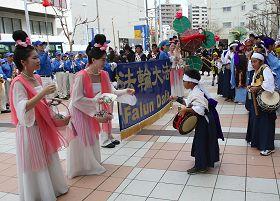 天國樂團在旗頭陣現場演奏,仙女並發送繫有「法輪大法好」卡片的蓮花書籤。