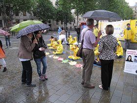 民眾冒雨觀看法輪功學員的功法演示