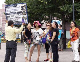 '退休宜蘭教師李光輝正向中國遊客講真相(身著黃色襯衫拿展板)'