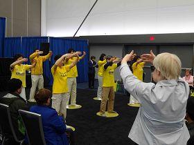法輪功學員演示功法時,觀眾現場學煉動作