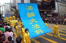 學員手持「法輪大法好」大幡,在九龍市區走過。