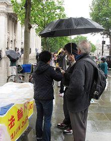 圖4:法輪功學員繼續冒雨徵集支持反迫害簽名。