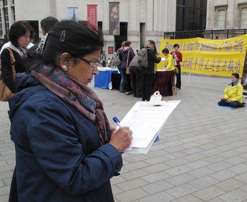 '印度裔女士薩迪娜(Satina)正在DAFOH徵簽表上簽字'