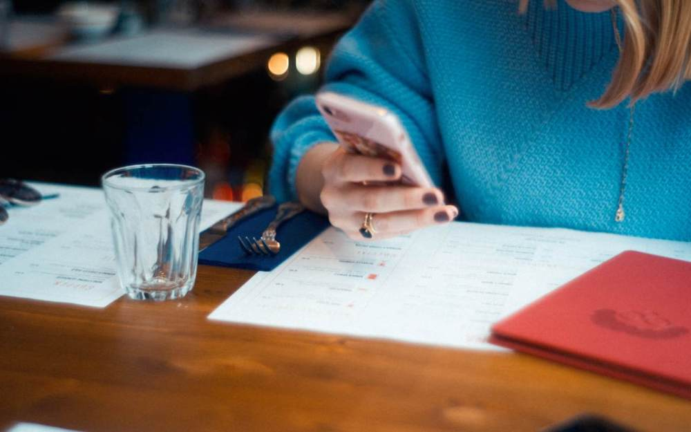 Social engagement - woman in blue jumper looks at phone in restaurant