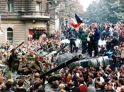 """TO GO WITH AFP STORY IN FRENCH BY JAN MARCHAL** Il y a quarante ans, le """"Printemps de Prague"""" étouffé dans le sang** (FILES) File picture of Czech youngsters holding a Czechoslovak flag standing atop an overturned truck as other Prague residents surround Soviet tanks in Prague on 21 August 1968 as the Soviet-led invasion by the Warsaw Pact armies crushed the so called Prague Spring reform in former Czechoslovakia. The Communist Party in Prague had declared """"democratic socialism"""" in the spring, upsetting the leaders of the other Warsaw Pact nations. At 4 a.m. on August 21, Soviet paratroopers surrounded the building of the Communist Party's central committee on the Vltava River and stormed reformer Alexander Dubcek's office. Soviet KGB officers then arrested the party leader. The tragedy had begun. AFP PHOTO HO/STR/FILES (Photo credit should read HO/AFP/Getty Images)"""