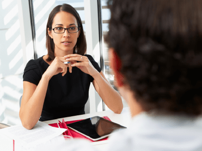 Picture of a young designer in a job interview. She is showing a hiring manager her portfolio. The designer looks nervous.