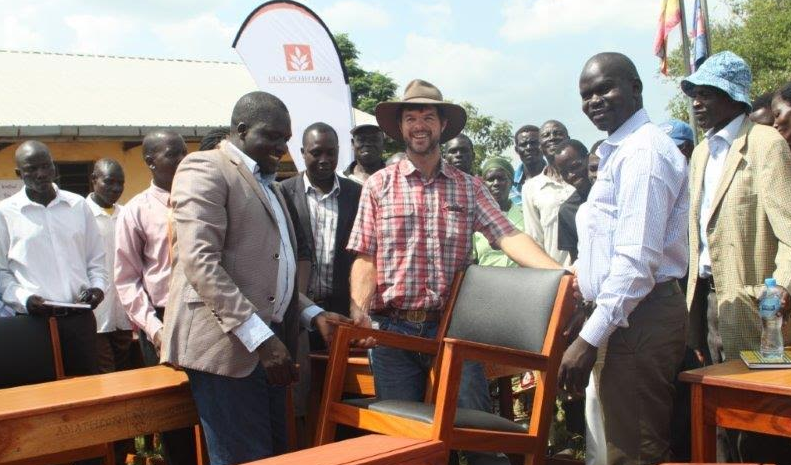 Jon McLea (in hat), the Managing Director of Amatheon Agri-Uganda Limited hands over furniture to Wii-Anaka Primary School in Nwoya district.
