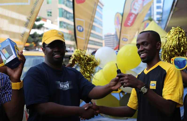 "MTN's Segment Manager Moses Musiime ( R )handing over the car key to Ben Namanya ( L ) 3rd year student from Makerere University after winning in the ongoing Data Campaign of ""Buy, Win and drive a car""."