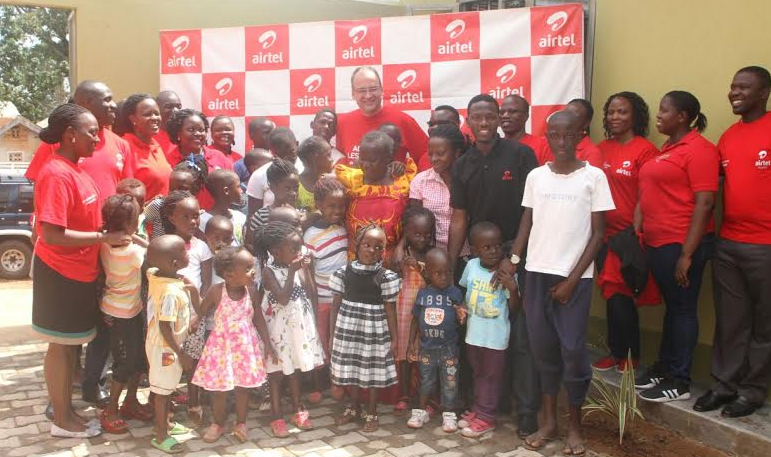 Jjajja Flora and her children pose with Airtel Uganda staff at the event to hand over a new house e built and furnished by Airtel Uganda.