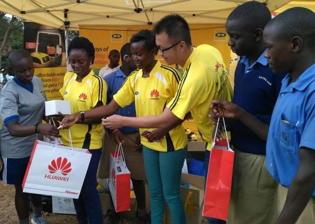 Paula Nansambu (2L), Account Manager Huawei Uganda, Jean Baguma (C), Huawei Uganda Marketing Manager and Derek Liu TeGuang (3R), Account Manager Huawei Uganda hand over smartphones to pupils of Uganda School for the Deaf-Ntinda aimed at aiding the pupils in their education and daily life.
