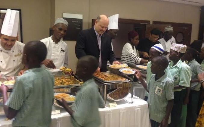 Sheraton Kampala Hotel's General Manager Mr. Jean-Philippe Bittencourt (In Black coat) serving some of the children that attended the Iftar diner yesterday in the Sheraton Ballroom.