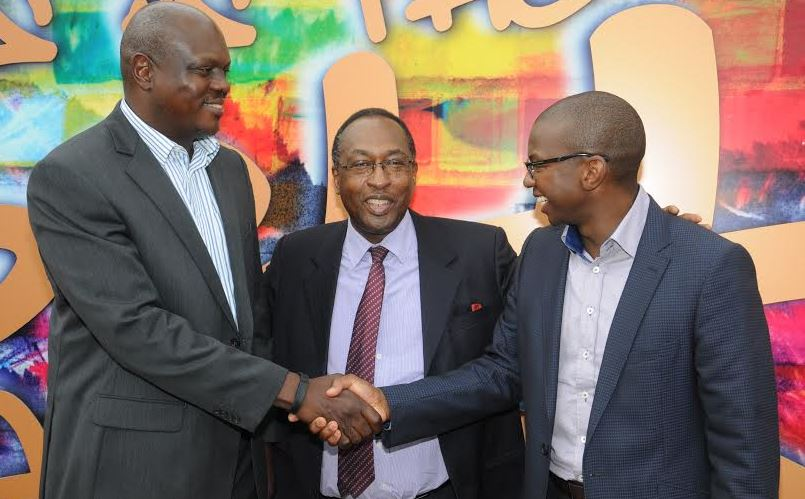 L-R: Mr. Mark Ocitti Ongom and Mr. Nyimpini Mabunda shake hands at a press briefing at which Uganda Breweries Limited (UBL) announced a change in leadership. Mark replaces Nyimpini as Managing Director of UBL effective August 1. Centre is the Board Chairman, Dr. Allan Shonubi.