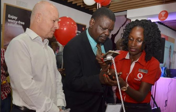 (R-L) The new Luwum Street Vodafone Experience Store manager- Deborah Namisango shows the KACITA spokesperson- Issa Sekitto one of the devices offered at the store as the CEO Vodafone Uganda, Allan Richardson looks on.