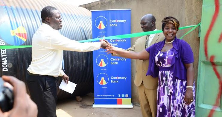 Mr Patrick Odhiambo, the Centenary Bank Bwaise Branch Manager, cuts the tape with Mr and Mrs Serunjogi, the proprietors of Malaika Orphanage Children Foundation in Kawempe.