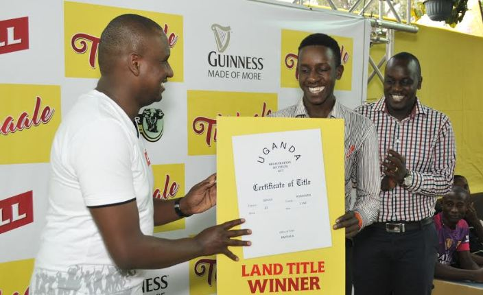 (L-R) Mark Mugisha, Head of Beer at Uganda Breweries Limited (UBL) hands over a dummy title to Aloyzious Kizza, 21 years old, who emerged winner of a plot of land in the ongoing Tubbaale promotion.