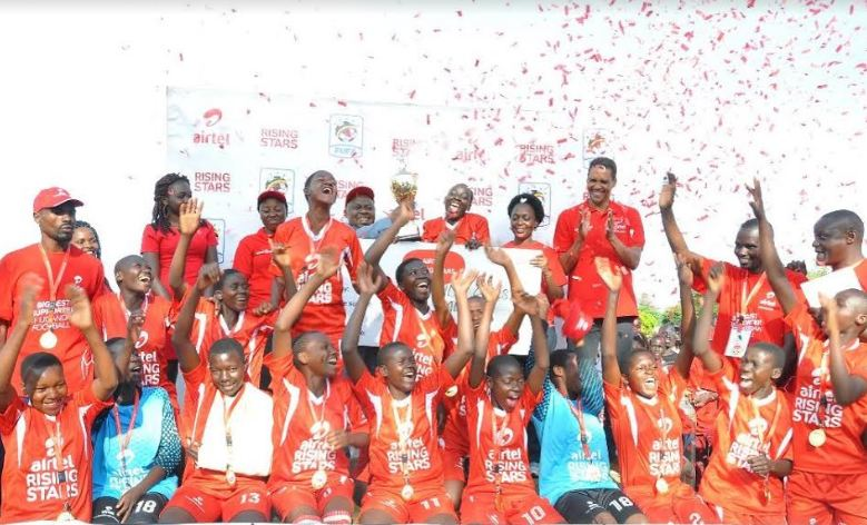 Buganda region girls celebrate after receiving their trophy and a dummy cheque of Ugx 5 million as winners of season six Airtel Rising Stars Nationals.