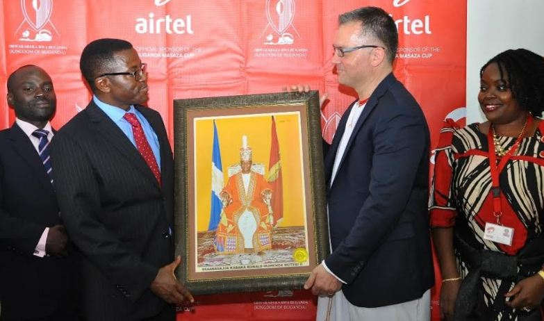Katikiro of Buganda Kingdom, Owek. Peter Mayiga hands over gift to Airtel Uganda MD Anwar Soussa as Buganda Kingdom and  Airtel Uganda officials look on at the official announcement  of Masaza Cup sponsorship