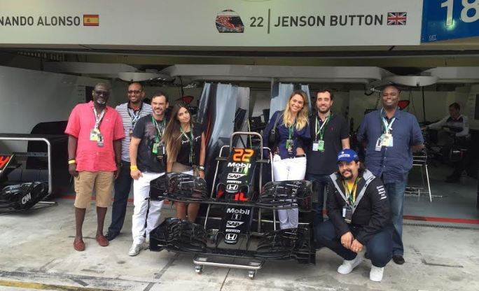 The Blue Club members pose by one of the Formula One Cars.