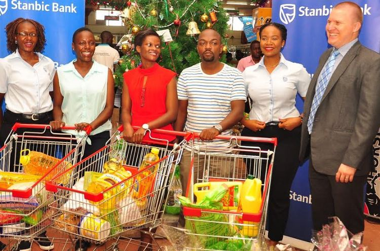 Stanbic Bank staff Damalie Sajjabi(left),Unnie Luwaga (2nd right) and Wayne Cook(right) pose for a picture with the three lucky winners of the first StanbicXmasDash campaign draw at the Capital Shoppers in Ntinda,Kampala