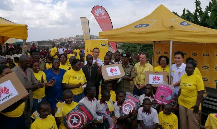 Assistant Inspector General of Police Asan Kasingye handing over a laptop to the administration of Kireka Barracks School as MTN CEO Mr. Wim Vanhelleputte, MTN partners and students witness.