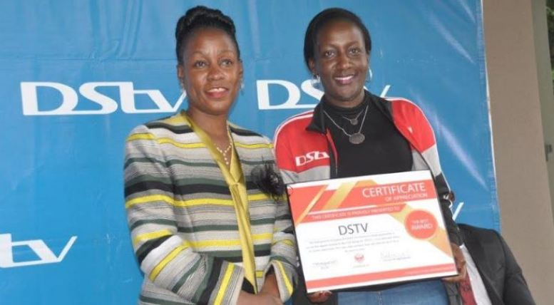 Hon. Minister Florence Nakiwala Kiyingi, Chairperson of Express FC poses with Phoebe Nakabazzi, Marketing Manager DStv Uganda after presenting a a certificate of appreciation.