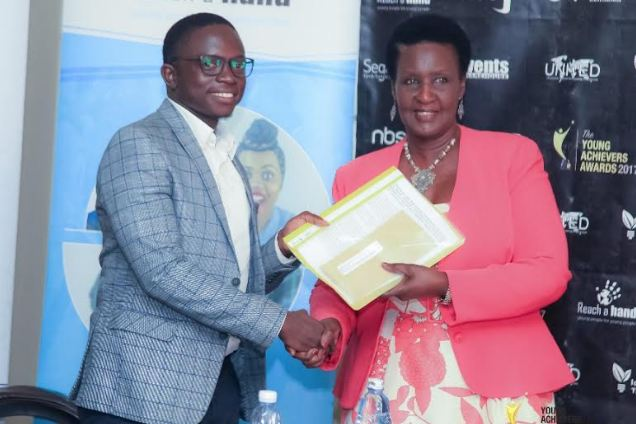 Gerald Otim, winner of the Innovations & ICT receiving his support receives his cash prize from Hon. Amelia Kyambadde