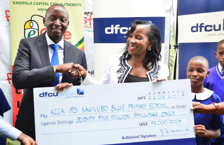 William Sekabembe, dfcu Bank's Executive Director and Head of Business hands over a dummy cheque to KCCA Executive Director, Jennifer Musisi