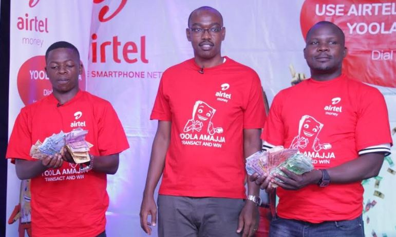 Airtel Money Marketing Manager, Nelson Mugisha (middle) pose with the winners.