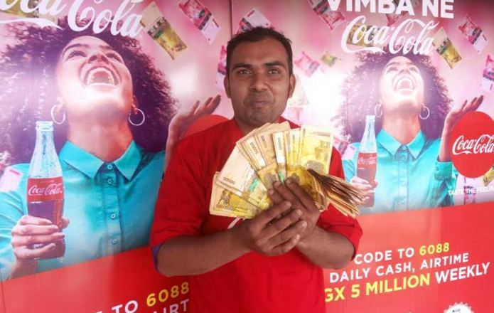 Ali Afijar, a resident of Entebbe, displays the cash he won in the Vimba ne Coca-Cola promotion