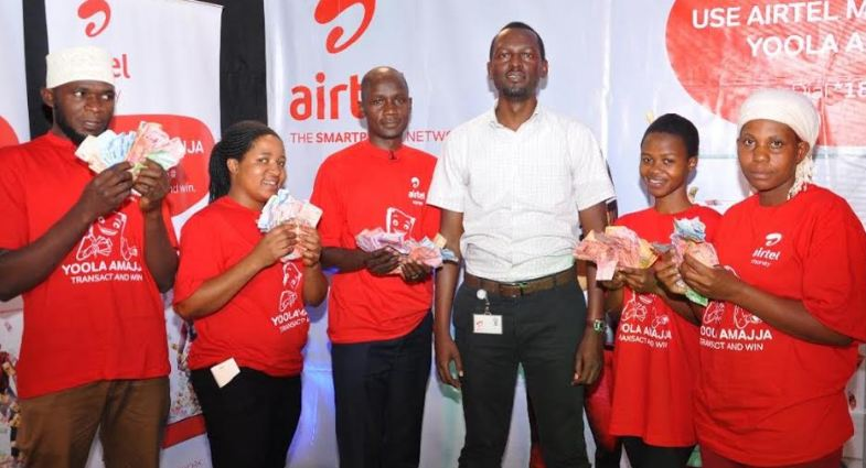 Airterl Money Settlements Manager, Yosia Mulumba, (3rd right) with the winners in the final draw of the Yoola Amajja draw.