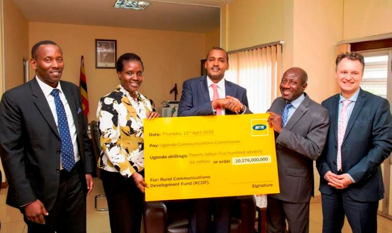 Hon. Frank Tumwebaze (C), Cabinet Minister of Information Technology and Communications (ICT), receives a dummy cheque worth UGX 20.5Bn from Mr. Ebenezer Asante the MTN Group Vice President of Southern & East Africa and Ghana (SEAGHA) region (second from left).