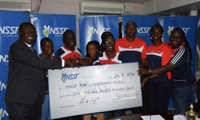 NSSF Deputy Managing Director Patrick Ayola hands over a dummy cheque to KAVC's Technical Director Shillah Buyundo at Workers House.