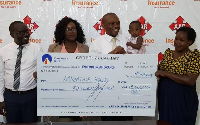 A team from AAR insurance hands over a dummy cheque to Aria's parents.