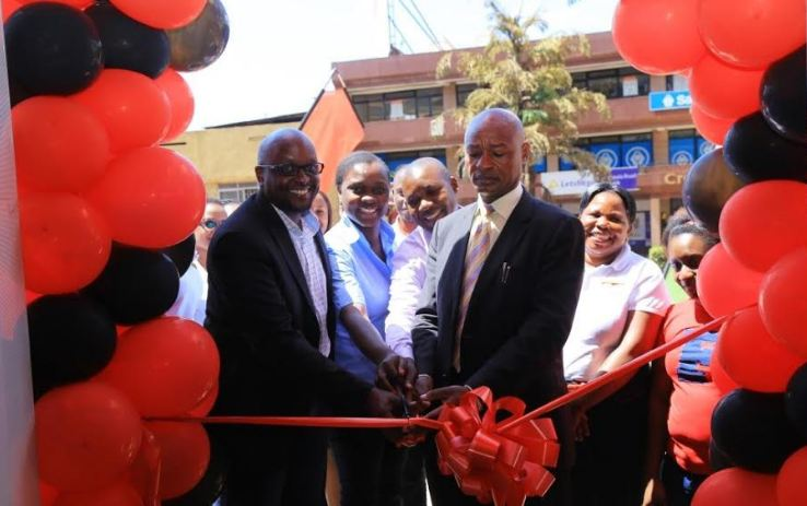 Airtel Uganda Legal Director Dennis Kakonge (L) joins staff and customers to open a new premium shop at Thobani building in Kampala