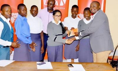 UBA Head Retail Banking, Paul Luyima hands over literature books to students of Fort Portal Secondary School.