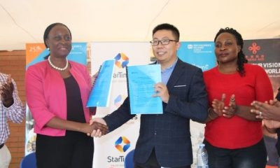 Olive Lumonya (L) exchanges MOU with Andy Wang (M) as StarTimes PRO Christine Nagujja looks on.