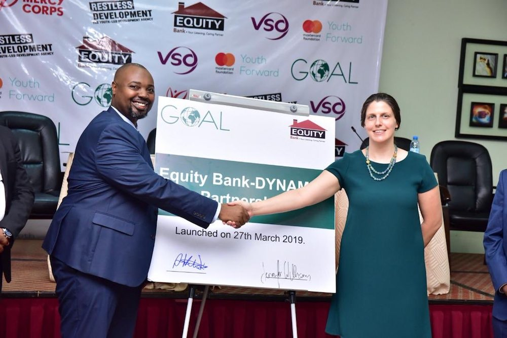 Equity Bank Uganda Executive Director Mr Anthony Kituuka and Jennifer Williams Country Director GOAL sign a plaque at Imperial Royale Hotel in Kampala to launch the Equity Bank DYNAMIC partnership.