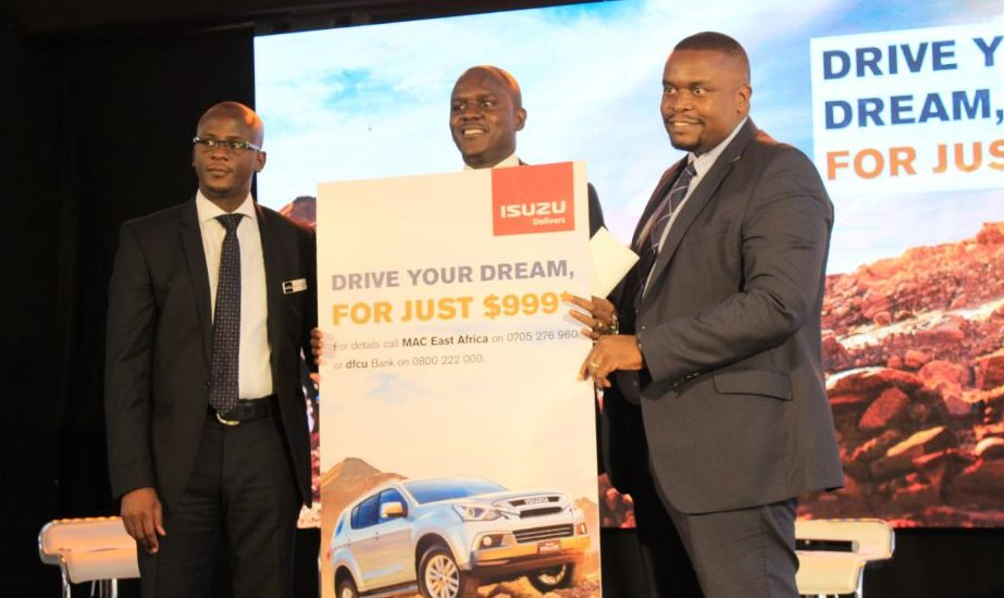 Kawalya Douglas Head Tender Sales MAC East Africa Ltd, dfcu Bank's Ronald Ssonko Asset Finance Manager and Daniel Kairu Head of Business Developmetn ICEA unveiling the offer at Isuzu showroom.