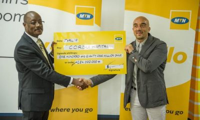 Acting MTN Uganda CEO Mr. Gordian Kyomukama (L) hands over a UGX 184m cheque to improve the quality of life for children with disabilities to CoRSU Hospital CEO Dr. Davide Naggi
