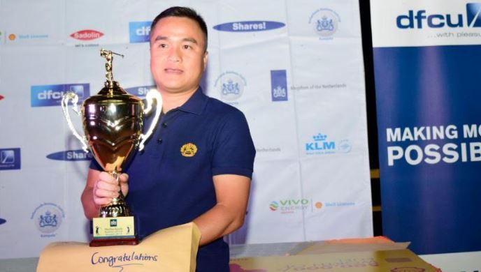 Wu Wei Ling poses for a picture with his trophy on the podium.