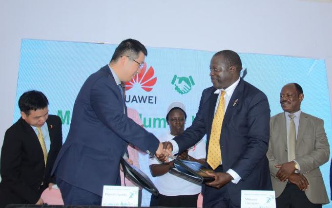 Huawei MD Liujiawei and College of Computing Principal Tonny J. Oyana shake hands after signing an MoU to establish an ICT Academy at the university.